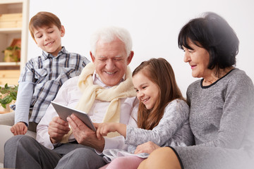 Grandparents and grandchildren using tablet
