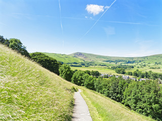 From a half way up steep Derbyshire hillside the town of Castleton can be seen sitting below, the view continuing over trees, fields and meadows to Mam Tor in the distance.