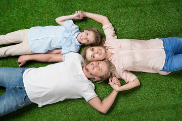 above view of happy family looking at camera while lying on the grass