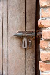 Old metal door lock on wooden door