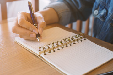 woman's hands writing in spiral notepad placed on wooden desk.
