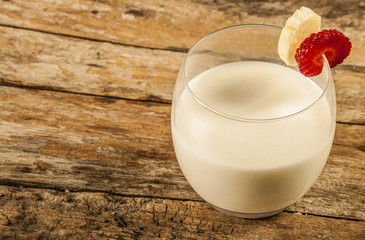 Fresh milk on wooden table over wall background