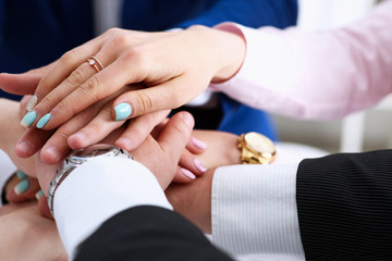 Group of people in suits crossed hands in pile