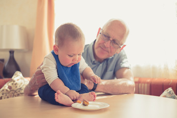 Grandfather helping baby learning to eat solids