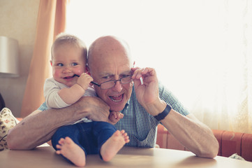 Grandfather playing with baby at table