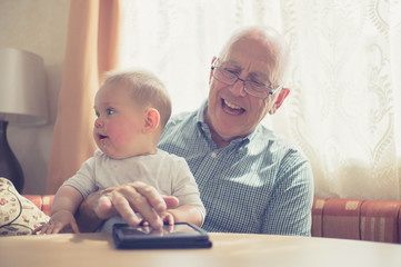 Grandfather with grandchild at table using tablet
