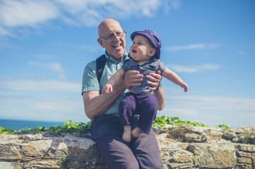 Grandfather playing with grandchild by the sea