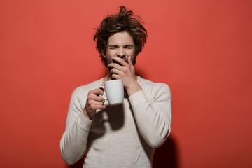 sleepy yawning man with cup of tea or coffee