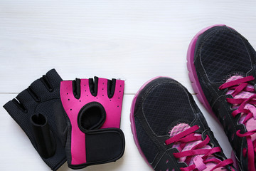 fitness concept equipment- sneakers and workout gloves on white wooden background