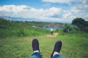 Feet of man relaxing on grass in nature