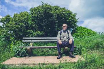 Senior man relaxing on bench in nature