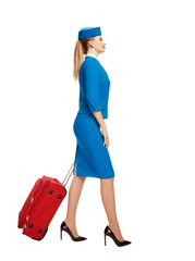The stewardess goes and rolls her suitcase.