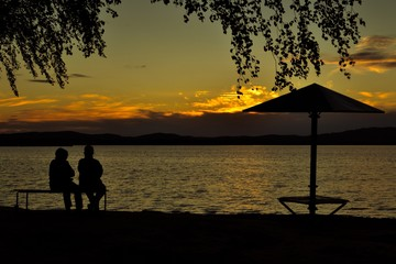 Two people are sitting on a bench on the beach and watching the sunset