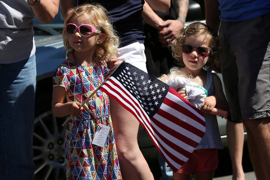 Girl holds U.S. flag watching parade marking Independence Day in Deer Isle