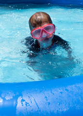 kid in goggles coming up for air in backyard pool