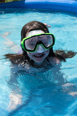 young girl in swim mask smiling in pool