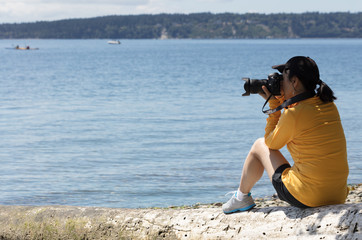 Woman photographer taking photos of calm lake during summer time