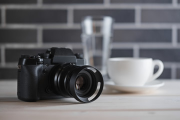 Selective focus lifestyle photo of camera on the table near cup of coffee