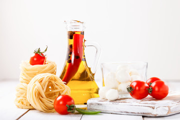 Olive oil with pepper in a bottle, paste, cheese and tomatoes on a light background. Selective focus. Copy space