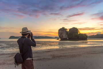 Young Asian man photographer taking photo of summer landscape with beautiful sunset sky at Ao Nang Beach, famous tourist attraction and travel destination of Krabi Province, Thailand
