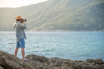 young Asian man photographer on the rock taking photos of tropical island during sunset, seascape for summer holiday and vacation travel concepts