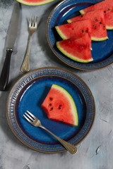 Pieces of watermelon on a dark blue plate. Grey background.