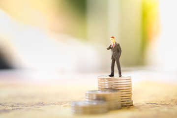 Money and Business Concept. Businessman miniature figure standing on top of stack of coins and looking forward to the future.