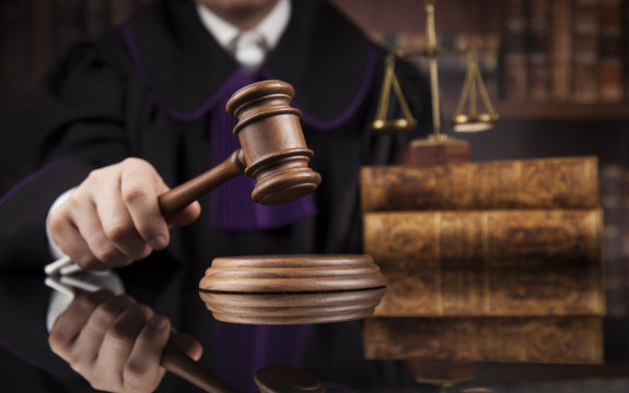 Justice and law concept, Male judge in a courtroom striking the gavel