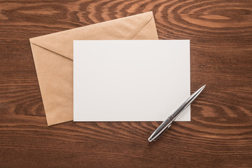 Envelope and  pen on a wood table