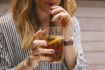 woman drinking iced tea with a straw