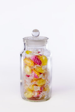 Confectionery. Jar of boiled sweets in wrappers isolated against white background. Yellow and pink candy.