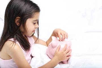 Beautiful little girl with piggy bank on white bed