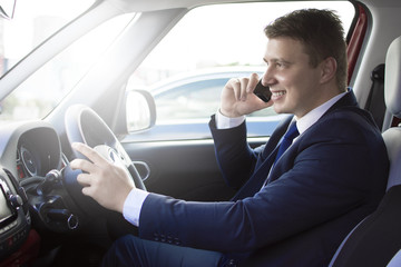 Businessman driving his car while talking on the phone. Smiling and talking while in traffic. Suit and tie businessman sitting in his automobile.