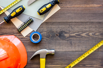 Tools for repairing and helmet on wooden desk background top view copyspace