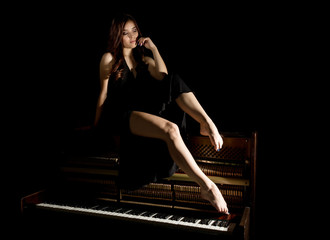 beautiful young woman in a black dress with an open back sitting on a old piano on a dark background