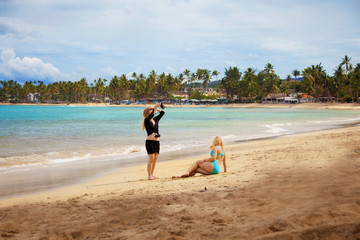 girl traveller making the photo of another girl in bikini on the sandy beach