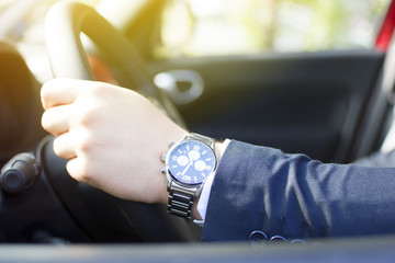 Close-up of a young businessman hand on the steering wheel. Lens flare in the background. Businessman driving a car concept.