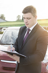 Closeup of a man filing a paper form on a clipboard. Modern businessman standing in a parking lot in front of the car. Lens Flare in the background.