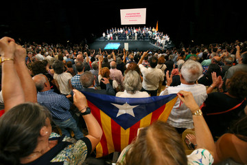 Supporters holds a flag during a meeting about the terms and conditions of the independence referendum in Barcelona