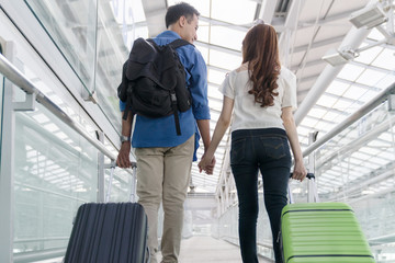 Young happy asian couple form back view  carrying suitcase luggage in airport terminal. Couple holding hand and traveling abroad together, Air travel or holiday vacation concept