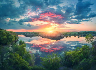 Wall Mural - Amazing scene with river, green trees, rocks and amazing blue sky with colorful clouds reflected in water at sunset. Fantastic summer landscape with lake, overcast sky and yellow sun in the evening
