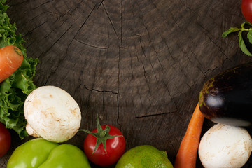 Fresh raw Vegetables on wooden stump. Bio Healthy food, herbs, spices, Carrots, aubergine, lettuce, tomato, mushrooms, Bulgarian pepper.  Organic vegetables on wooden background with copy space.