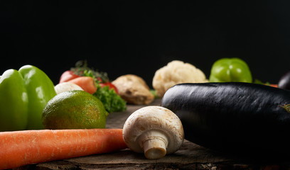 Assortment of fresh vegetables close up. Detox and healthy eating concept. Raw Vegetable on wooden table isolated on a black background with copy space.