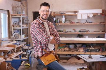 Young smiling carpenter in workshop