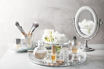 Composition of glass tray with perfume bottles and cosmetics on grey table