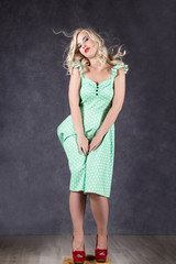 blonde woman with hair in the wind. sexy girl with flying hair posing in green dress and red shoes