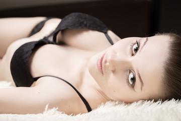 sensual beautiful girl lying on white fur, looking at camera