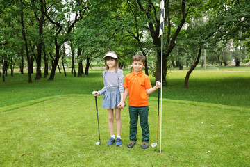 Cute children on golf course in summer day