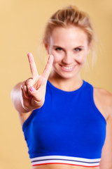 Beautiful fitness model showing victory sign