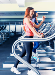 Smiling young woman with friends exercising on a treadmill